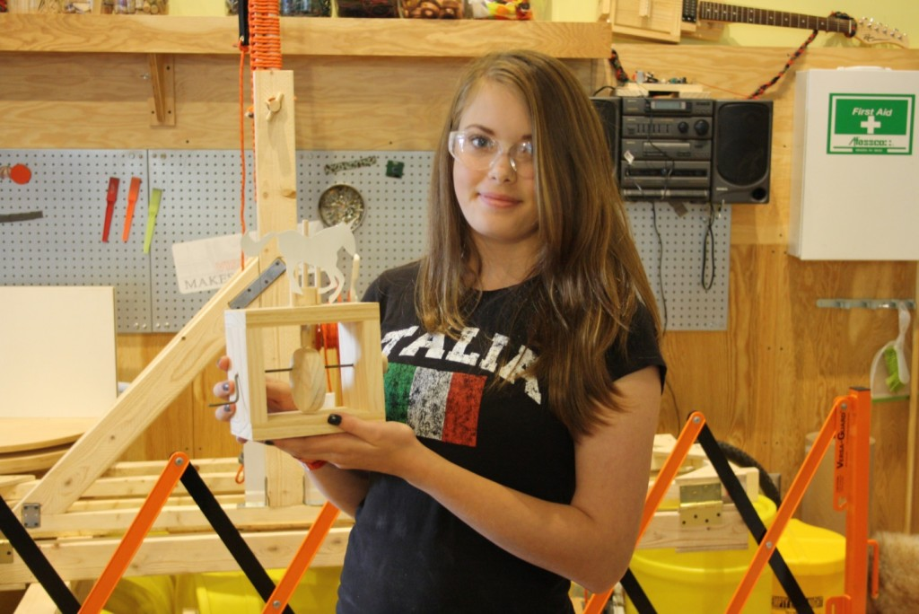 A visitor shows off her creation from 2013 Maker Corps Member Nick's Wooden Automata workshop. In the background is the baseball-tossing trebuchet we built with visitors to throw a first pitch for the Pittsburgh Pirates.
